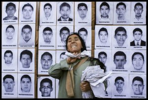 A protester stands in front of pictures of the disappeared students