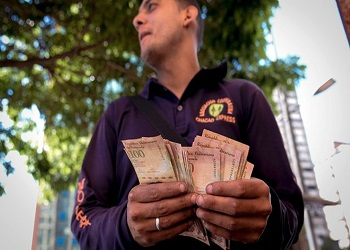 A man counting a stack of 100 bolivars bills