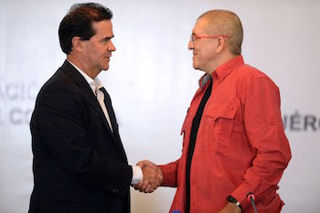 Government negotiator Frank Pearl (left) and the ELN's Antonio Garcia (right) shake hands in Caracas