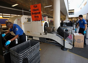 TSA agents screening luggage