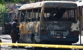 Police investigate a burned out bus in El Salvador