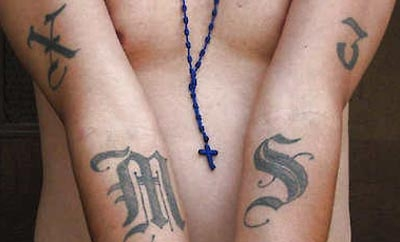 An MS-13 member in Washington displays his gang tattoos