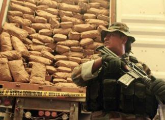 A Bolivian soldier guards cocaine seized from a Santa Cruz laboratory in February