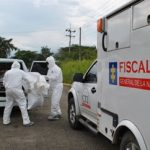 Officials remove bodies from the crime scene in Roldanillo