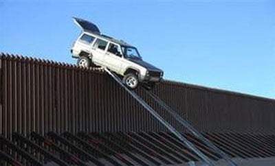 An SUV stuck on the border fence in California