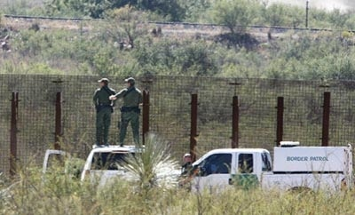 Two US Border Patrol agents survey the border