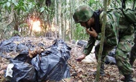 A Colombian soldier destroying a drug lab