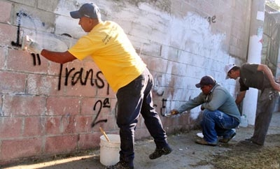 Gang members, government workers clean graffiti outside San Salvador