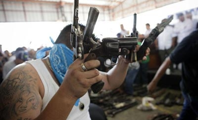 Gang members surrendering weapons in a ceremony