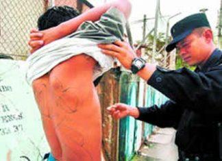 Police search a man in El Salvador