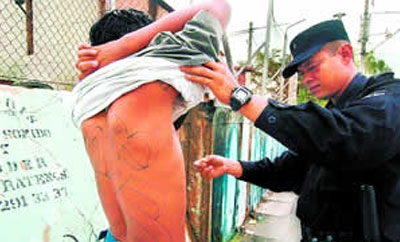 Police search a man in El Salvador