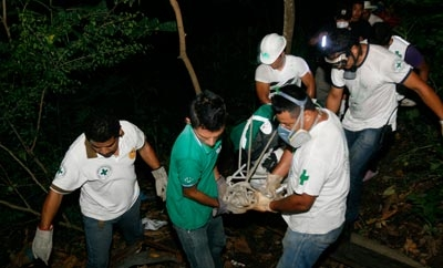 El Salvador police remove the body of a murder victim