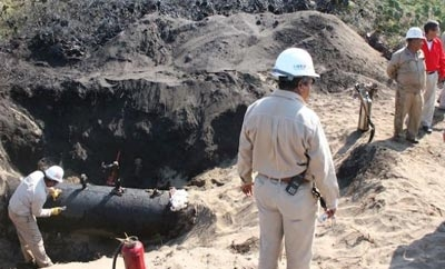 Pemex workers inspect an oil siphon