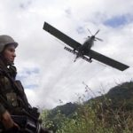 A Colombian soldier patrols an area being aerially fumigated