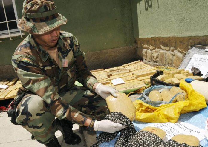 Bolivian anti-narcotics policeman with seized cocaine