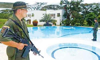 Colombian soldiers guard property seized from the FARC