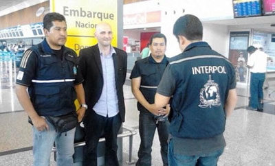 Valentino Alampi (in black) is arrested by Interpol