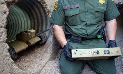 A US Border Patrol agent with a tunnel robot