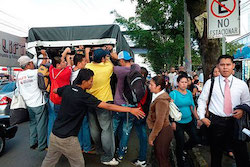 Salvadorans climb onto a pickup truck during the bus strike