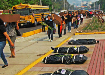 Marchers walk past body bags in Honduras