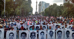 Protestors carry photos of the Iguala disappeared