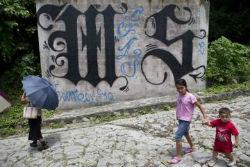 Children walking past MS13 graffiti