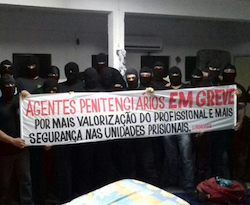 Striking prison guards in Ceará hold a sign proclaiming their demands
