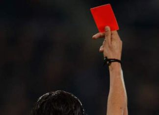 A soccer referee holds a red card, signifying a player is expelled from the game