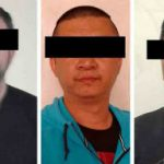 The recently detained migration official, left, and two Chinese nationals