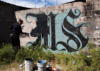 An MS13 graffiti being painted over by an official in El Salvador