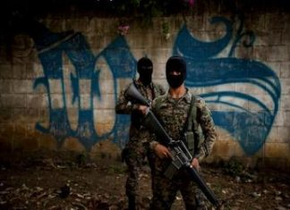 Security forces in front of MS13 graffiti