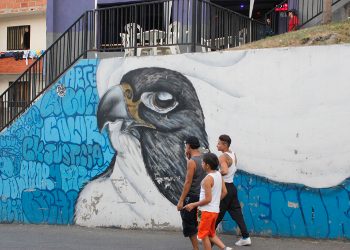 Young men walk past a mural in Comuna 13 depicting white flags that represent peace.