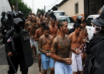 Gang members guarded by policemen outside El Salvador prison