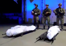 Colombian security forces pose with the bodies of David and his sister