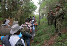 A Colombian soldier directs displaced community members