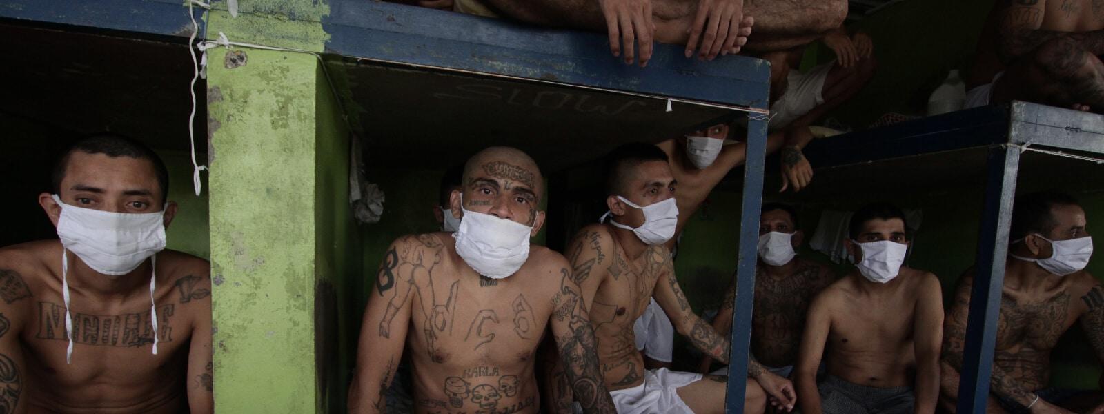 1.-El-Salvador_Imprisoned-gang-members-wearing-protective-face-masks-sit-inside-a-group-cell_AP_20335158061131_2020_Gamechangers.jpg